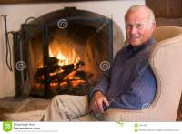 Man Sitting In Living Room By Fireplace Smiling Stock ...