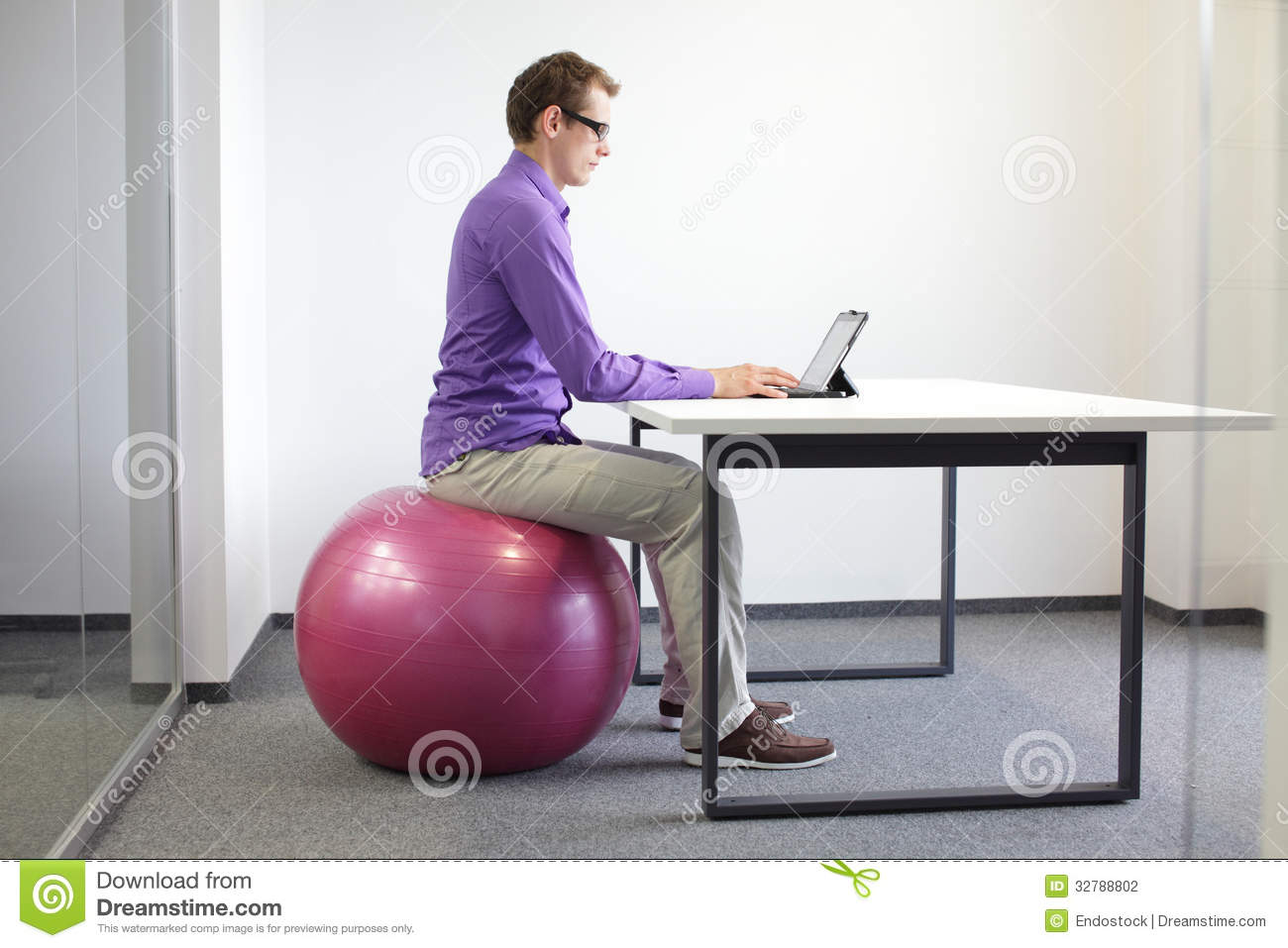Man On Stability Ball Working With Tablet Stock Photo