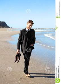 Man In Suit Barefoot Beach Holding Shoes Stock