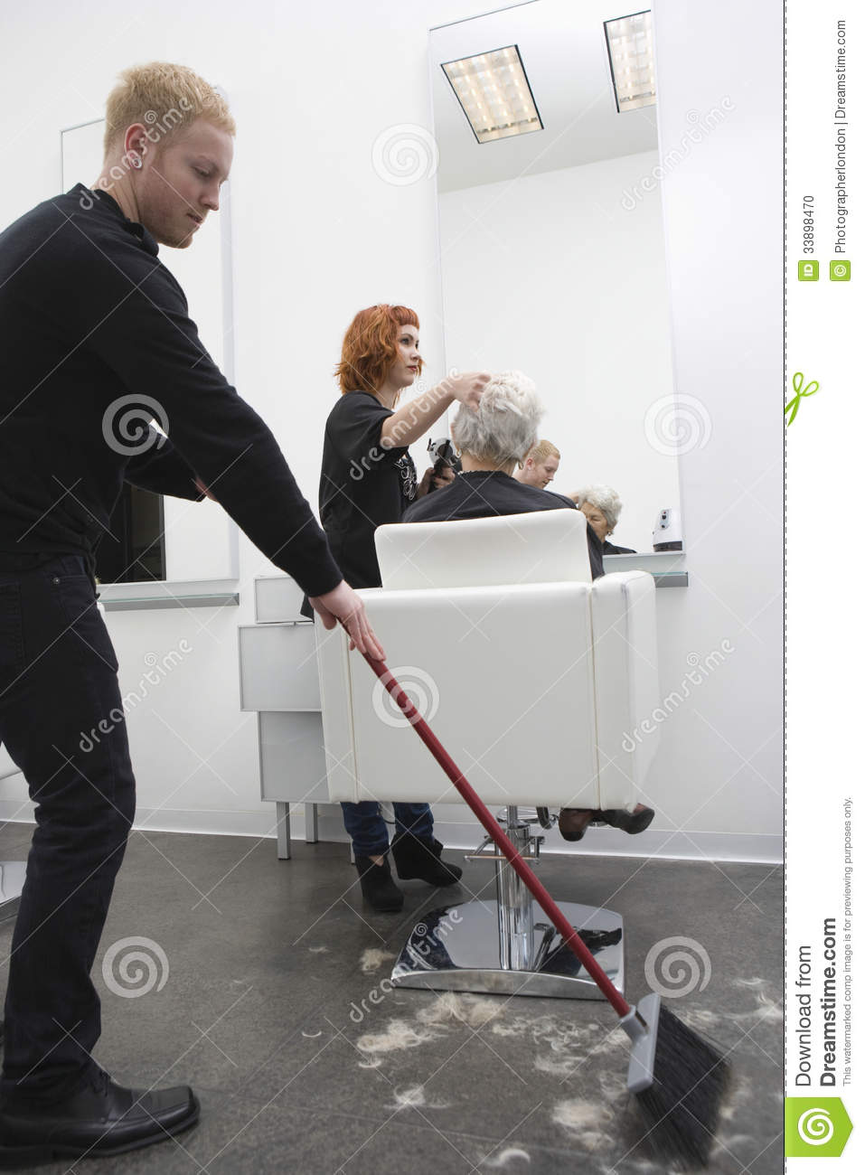 Man Sweeping While Hairdresser Giving Haircut To Senior Woman Stock Photo  Image 33898470