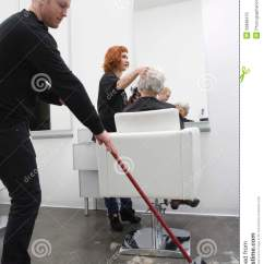 Chair For Barber Urinal Potty Man Sweeping While Hairdresser Giving Haircut To Senior Woman Stock Photo - Image: 33898470