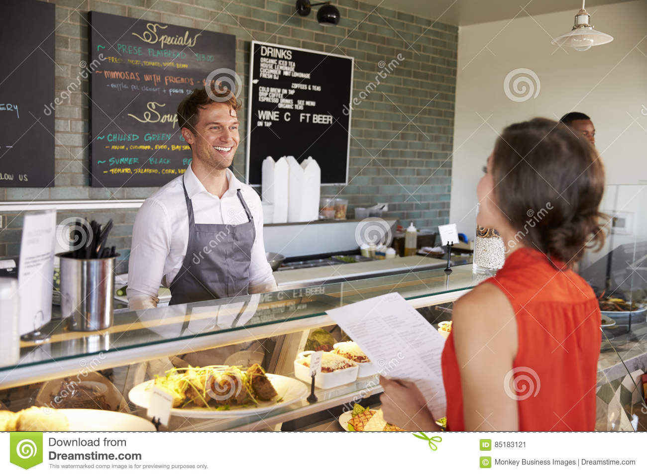 Man Working Behind Counter In Delicatessen Taking Food