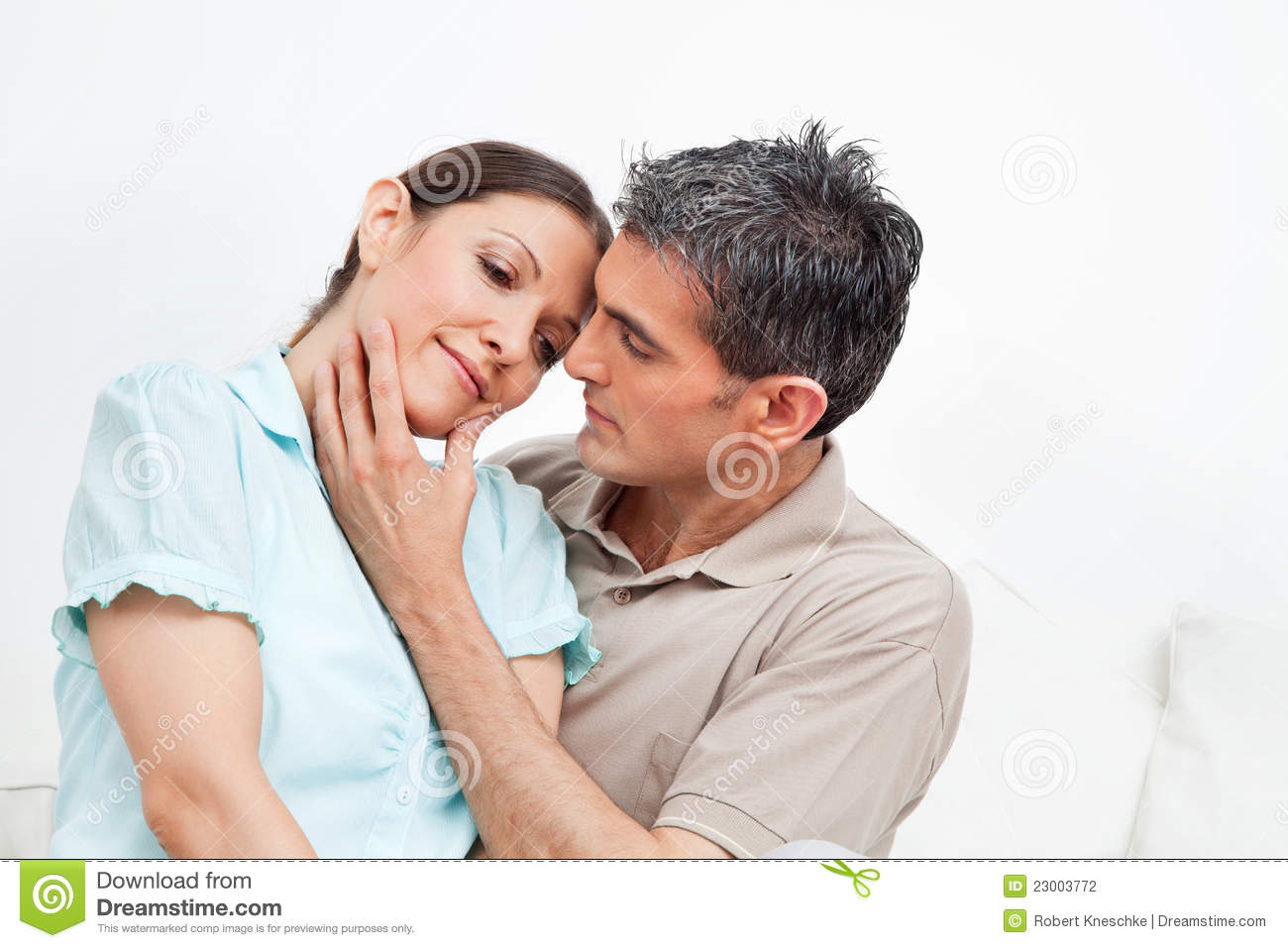 Married Couple Snuggling At Home Stock Photo
