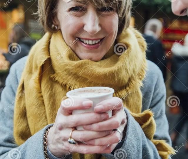 Mature Woman Drinking Hot Chocolate At Christmas Market