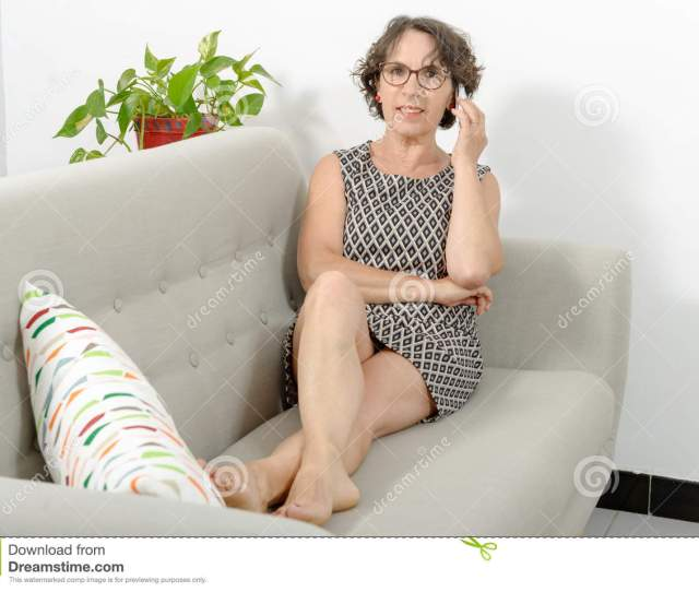 Mature Woman On The Sofa With A Phone