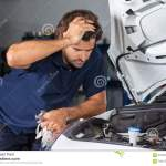 Mechanic Examining Car Engine At Repair Shop Stock Image