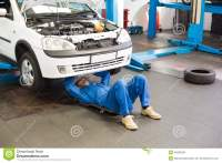 Mechanic Lying And Working Under Car Stock Photo