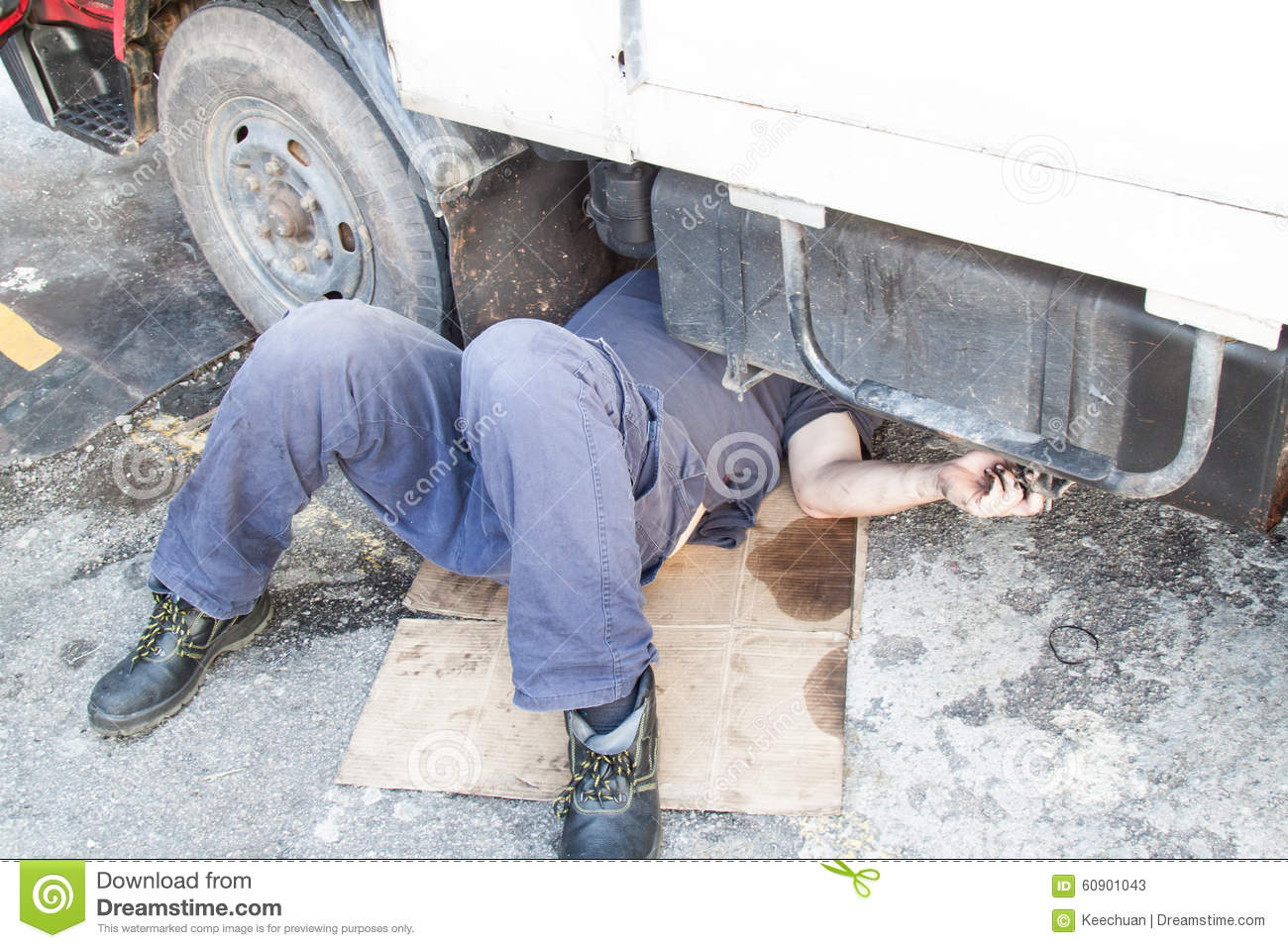 Mechanic Under Truck Reparing Dirty Greasy Oily Engine