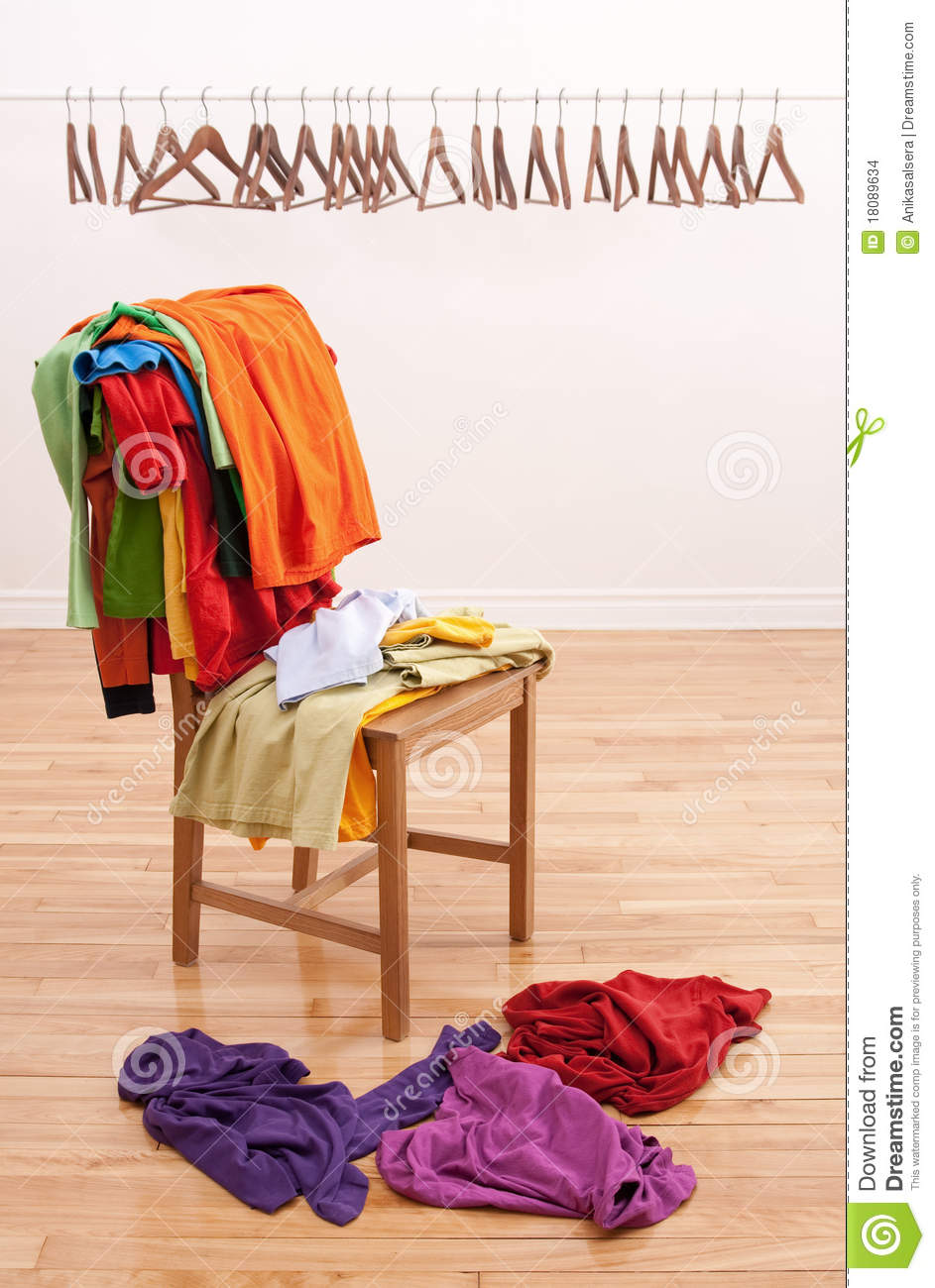 Messy Clothes On A Chair And Empty Hangers Stock Photo