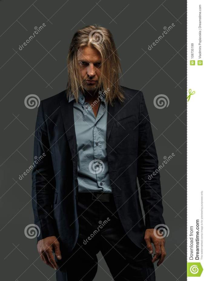 long hair man in suit possing. stock image - image of