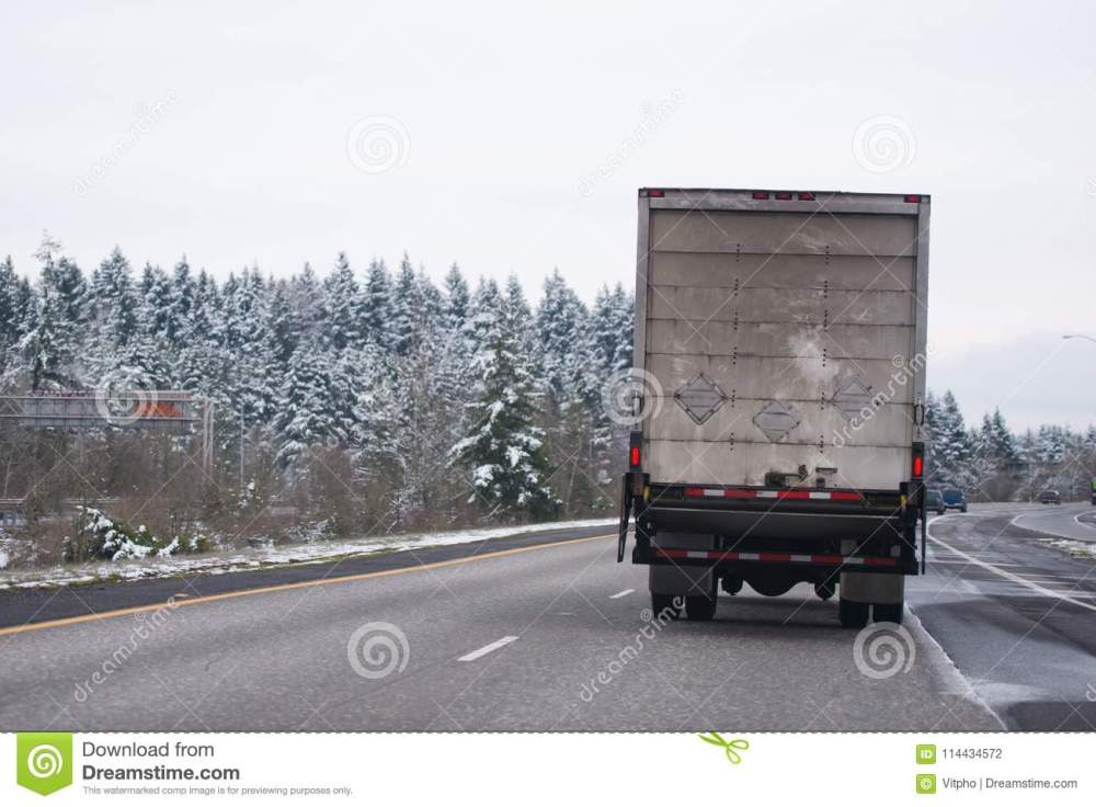 medium resolution of powerful middle size white day cab american made big rig semi truck with box cargo dry van trailer transporting industrial cargo and running on the wide