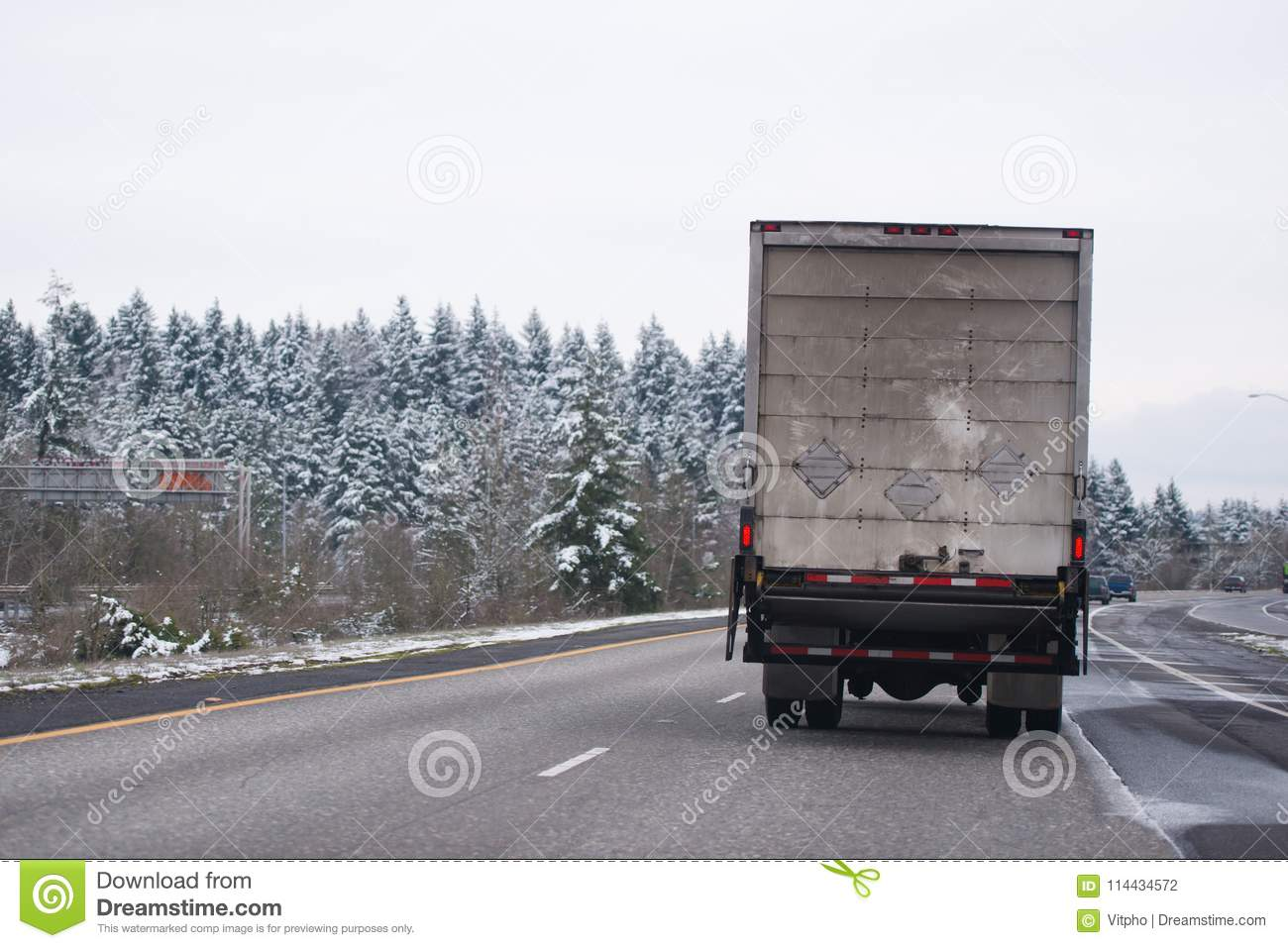 hight resolution of powerful middle size white day cab american made big rig semi truck with box cargo dry van trailer transporting industrial cargo and running on the wide