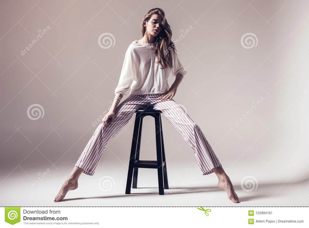 Chair Pants Model In Striped Pants And White Top Sitting On Chair Stock Image