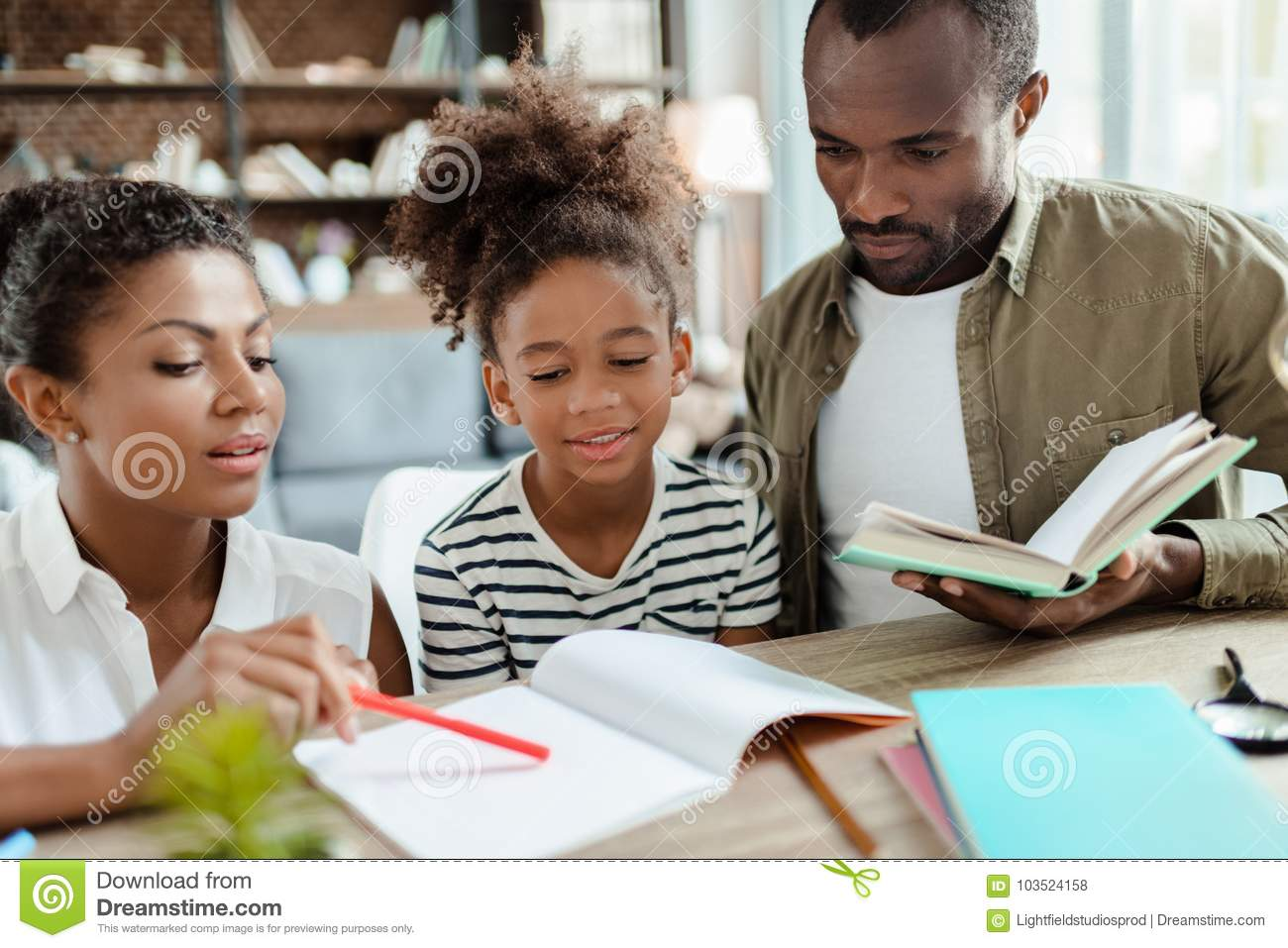 Mom And Dad Helping Daughter With Homework Stock Photo