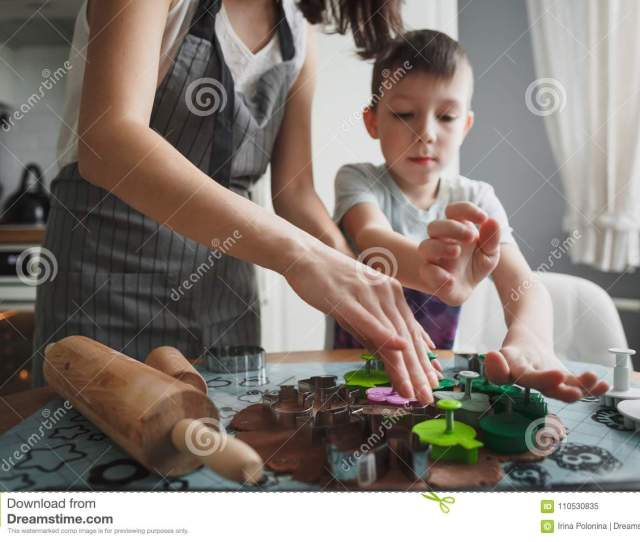 Mom And Her Son Cook Cookies In The Cozy Home Kitchen And Cut Cookie Molds