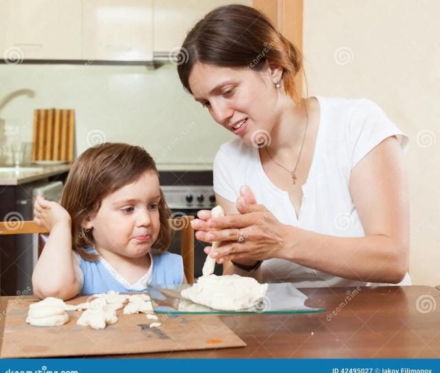 Mom Teaches The Girl To Mold Dough Figurines