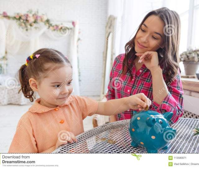 Mom Teaches A Little Daughter To Collect Money In A Piggy Bank
