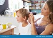mother brushing son's hair breakfast