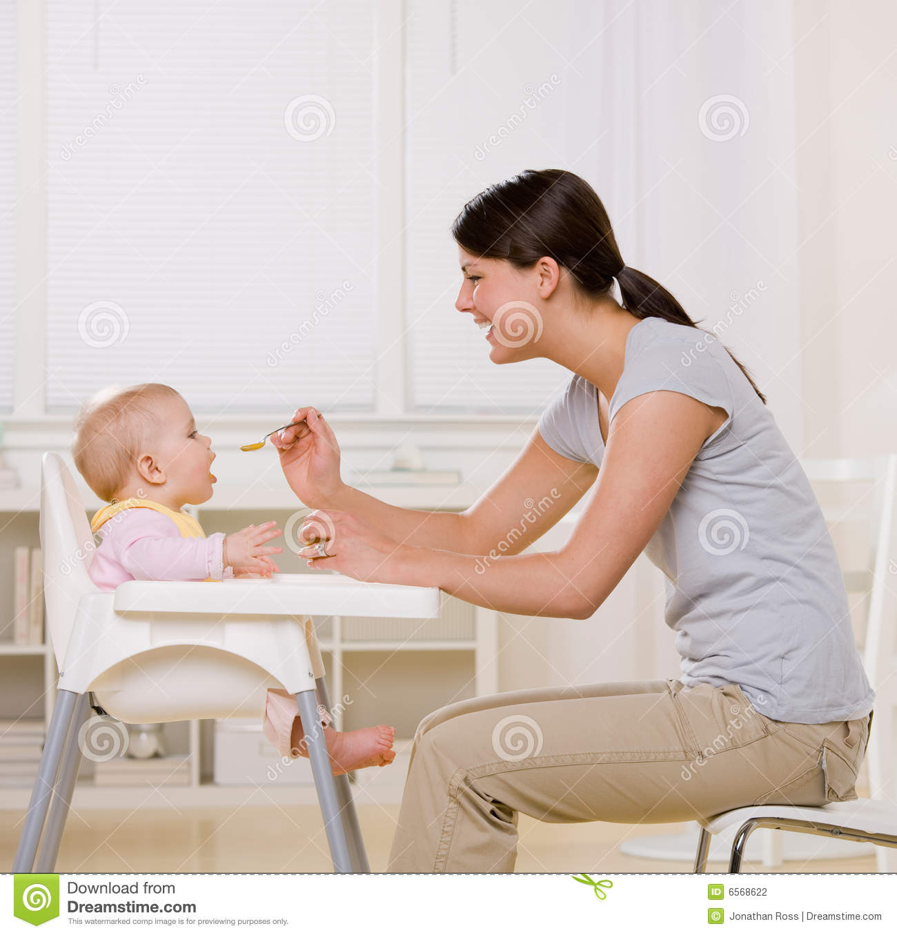 Baby Food Chair Mother Feeding Baby In Highchair In Kitchen Stock Photo