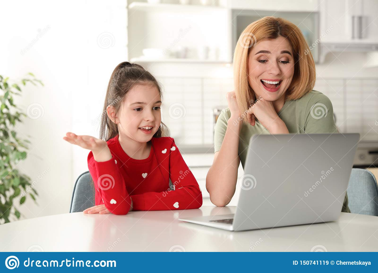 Mother And Her Daughter Using Video Chat On Laptop At