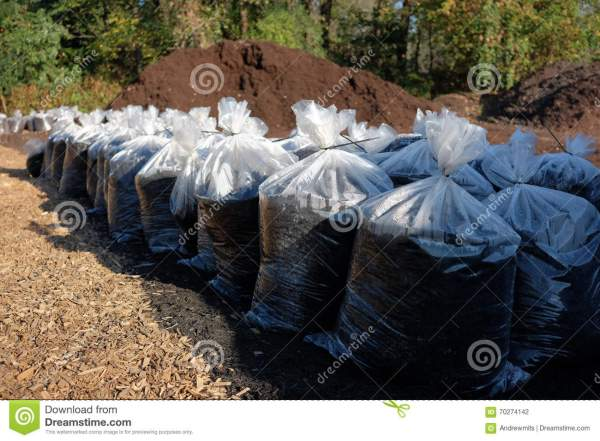 mulch pile with bags of stock