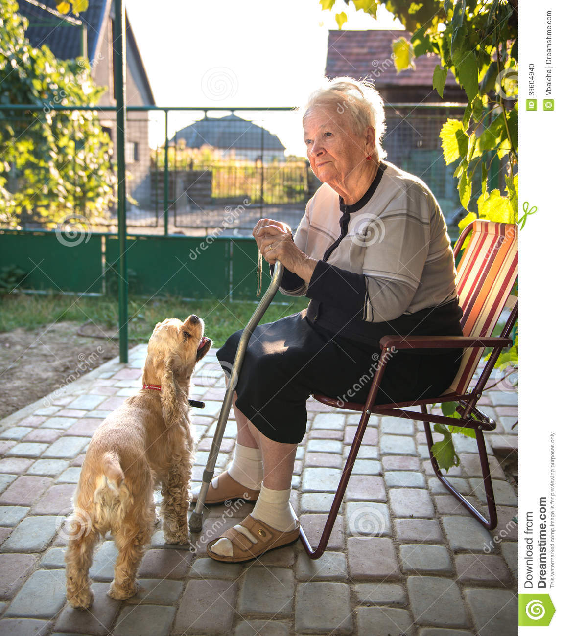 Old Woman Sitting On A Chair With A Cane Stock Photo