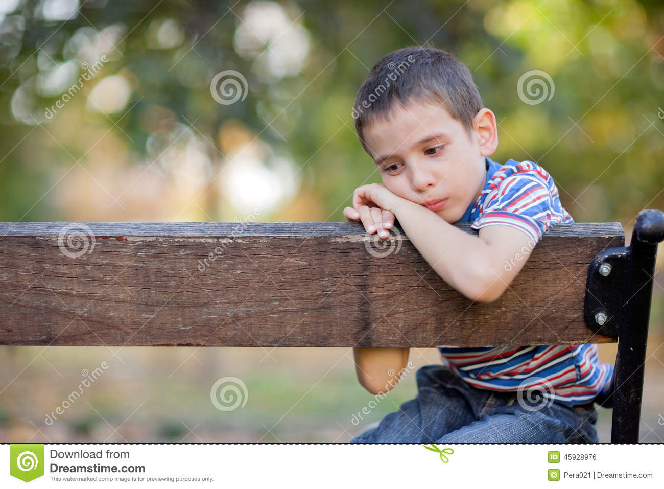 Orphan Unhappy Boy Sitting On A Park Bench And Crying