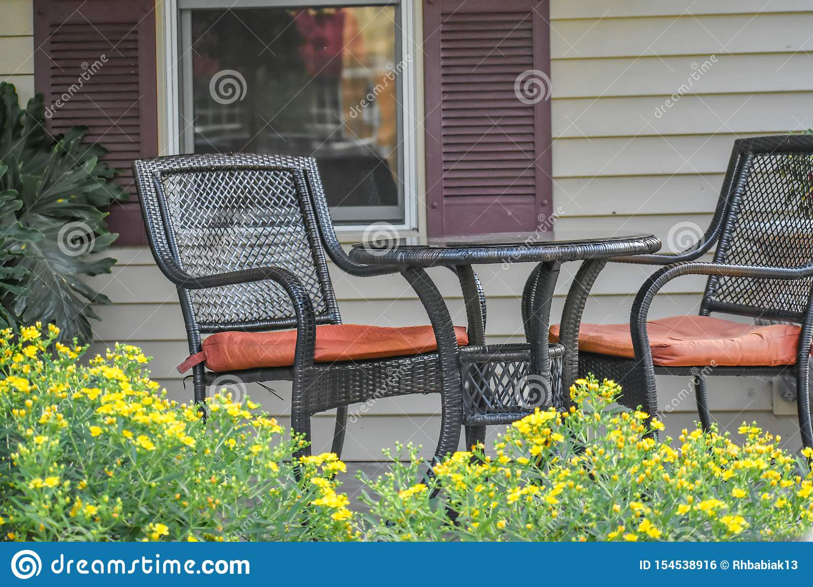 https www dreamstime com patio table chairs yellow flowers black wicker set two sitting front porch blooming int landscaped gardens image154538916