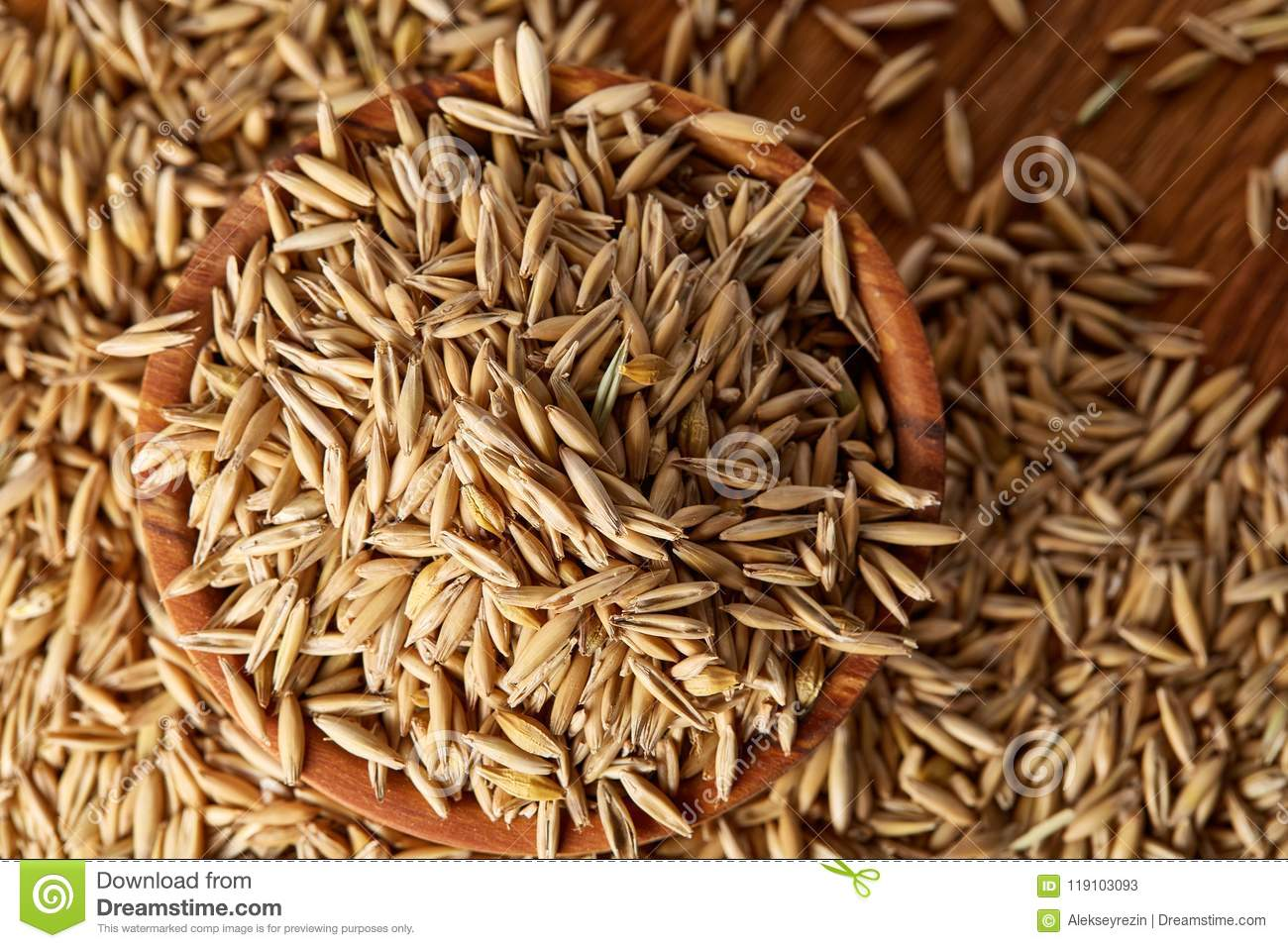 hight resolution of pile of unpeeled oat grains on wooden background top view close up macro selective focus shallow depth of field some copy space dietary food