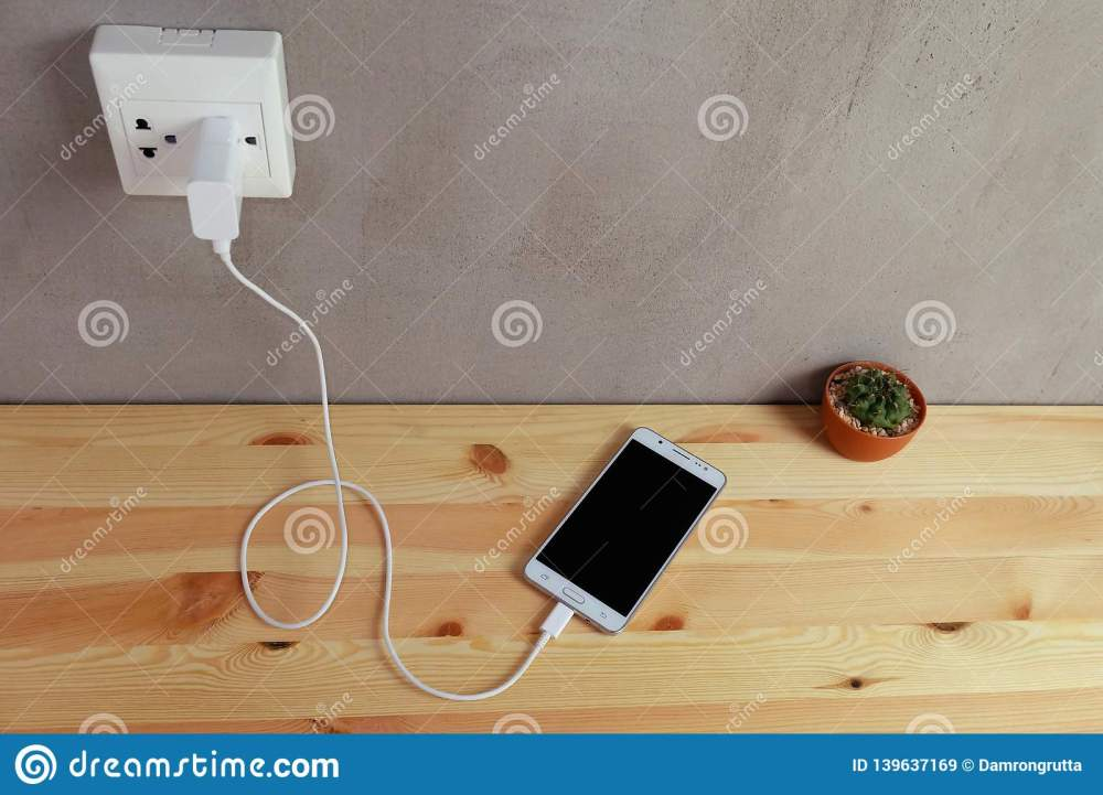 medium resolution of plug in power outlet adapter cord charger of mobile phone on wooden
