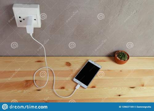 small resolution of plug in power outlet adapter cord charger of mobile phone on wooden