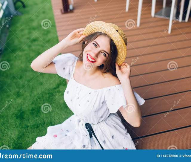 Portrait Of Pretty Girl With Long Hair In Hat Sitting On The Wood Floor Outdoor She Wears A White Dress With Nake