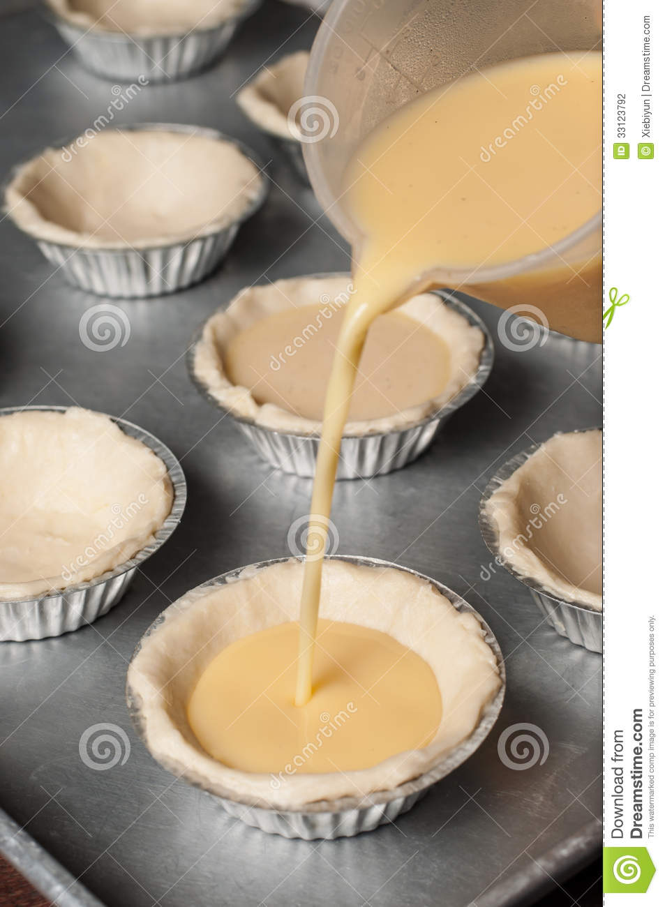 kitchen utensil refacing cabinets cost pour the egg custard mixture into each tart cup. stock ...