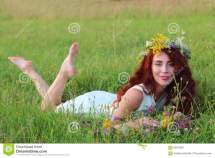 Pretty Woman In Wreath And Short Dress Lies Grass
