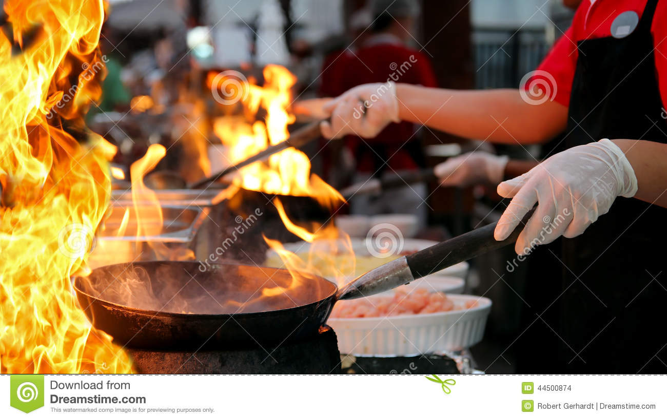Professional Chef In A Commercial Kitchen Cooking Flambe