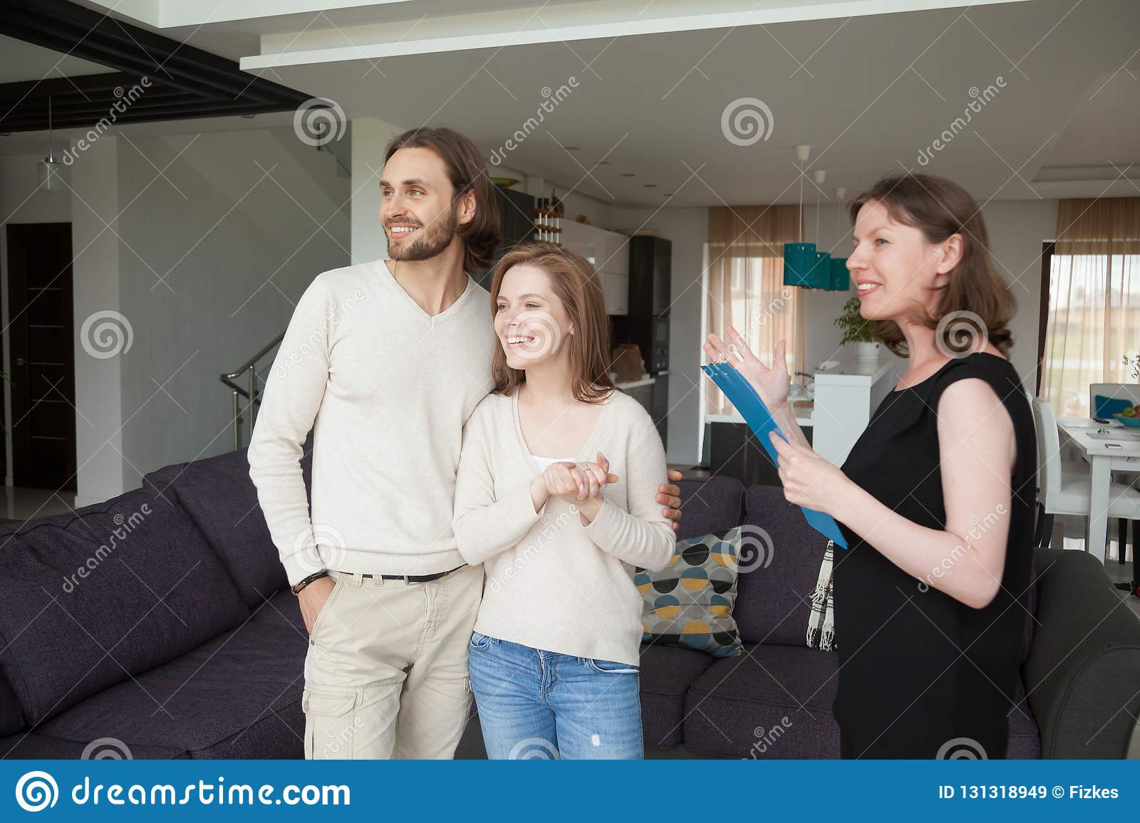 living room realtors lime green wallpaper realtor showing property for sale to young married couple stock three person standing in realestate agent house or tenant satisfied