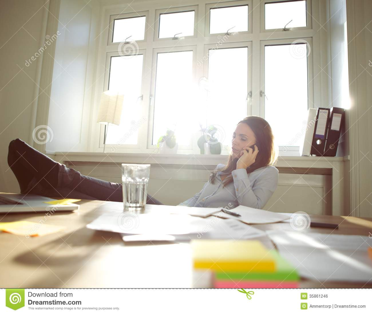 Relaxed Businesswoman Talking On Mobile Phone At Home