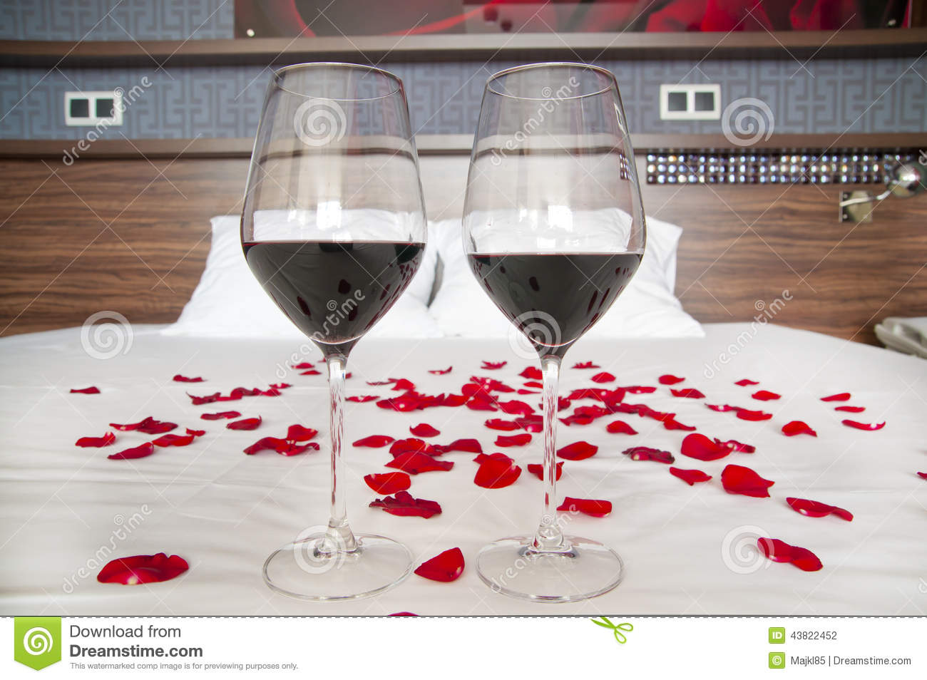 Romantic Bedroom Glasses Of Red Wine And Rose Petals On