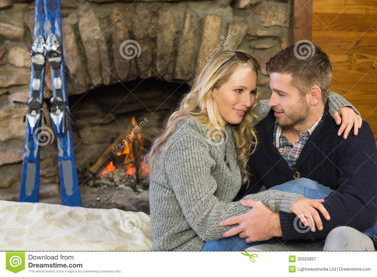 Couple Relaxing In Front Of Fireplace Man Looking At Woman Stock Romantic Couple With Arms Around In Front Of Lit Fireplace