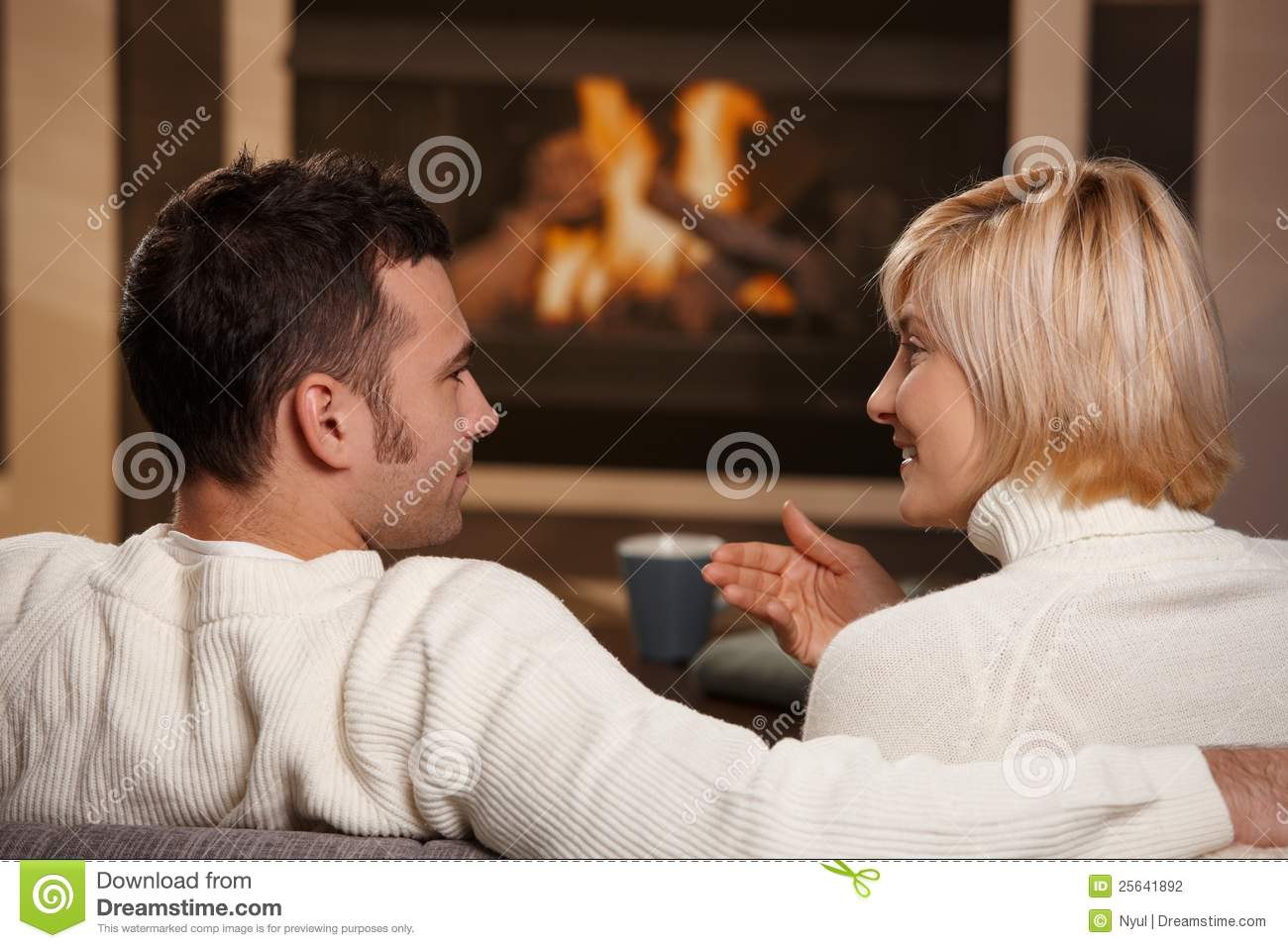 Couple Relaxing In Front Of Fireplace Man Looking At Woman Stock Romantic Couple At Home Stock Photography - Image: 25641892