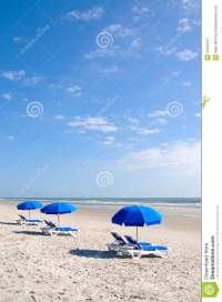 Row Of Beach Chairs With Blue Umbrella Royalty Free Stock ...