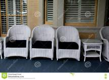 Row Of White Wicker Chairs And Tables Front Porch Stock
