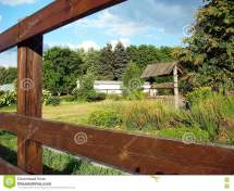 Rural Water And House Wooden Fence Stock
