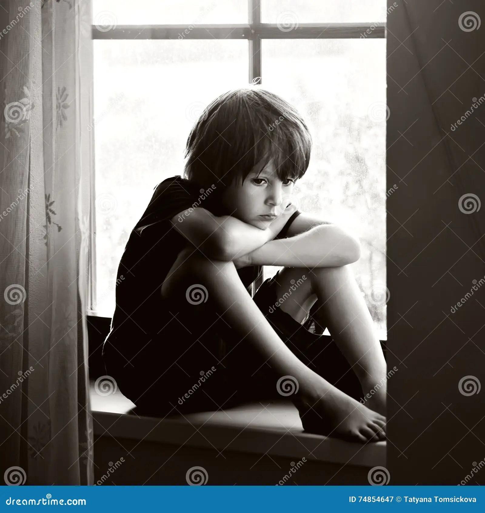 sad boy sitting window