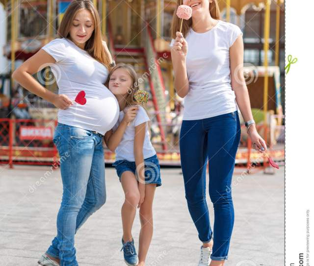Samesex Lesbian Family With Child On A Walk In The Amusement Park Lesbians Mothers With Adopted Child Happy Family Pregnant Couple With Kid