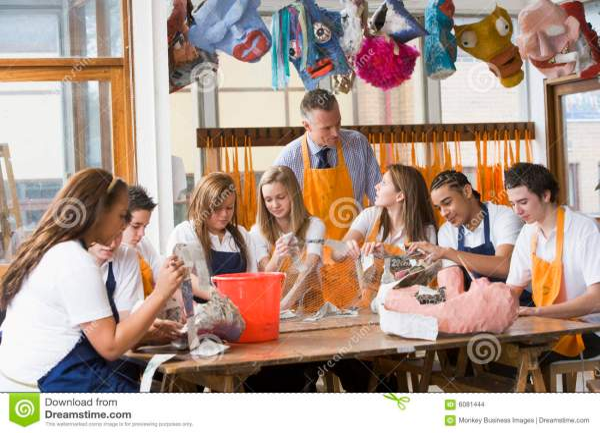 Schoolchildren And Teacher Sitting Table Stock