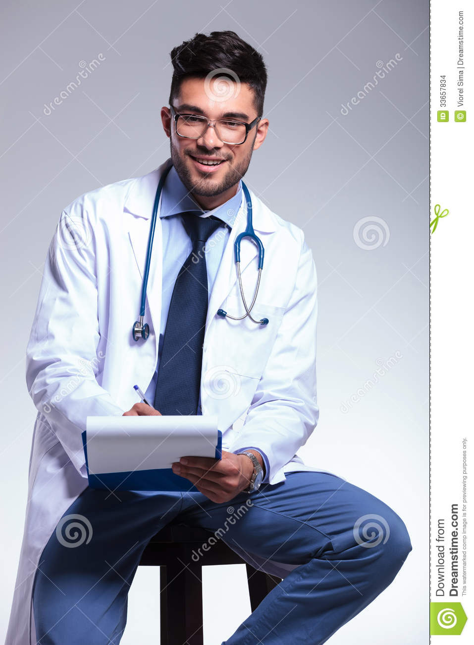 sitting chair hanging co.za seated young doctor writing on clipboard stock photo - image: 33657834