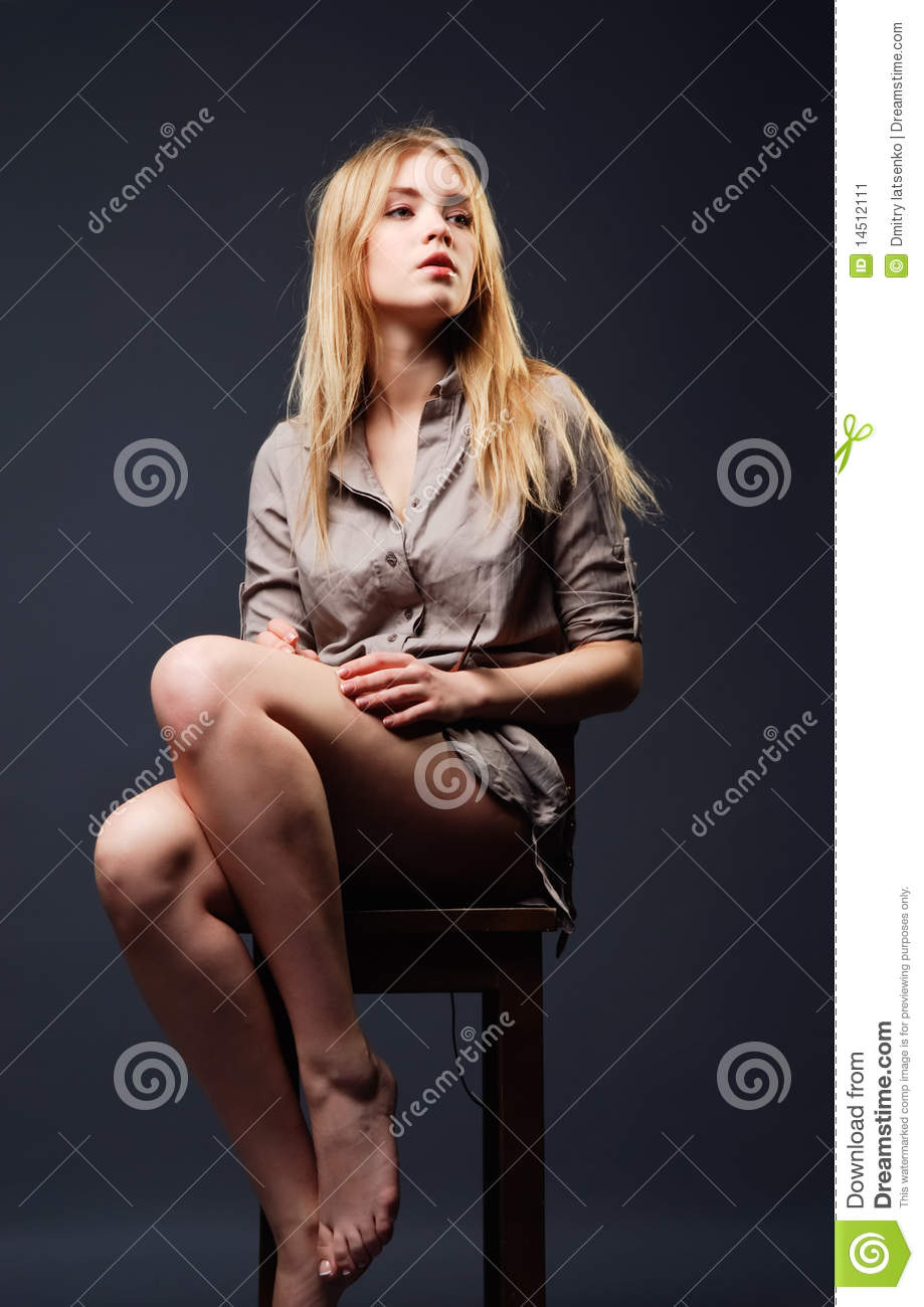 Seductive Portrait Of Young Woman Sitting On Chair Stock