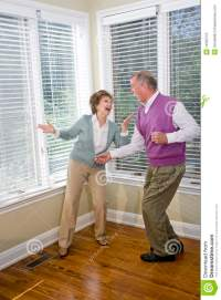 Senior couple having fun dancing in living room