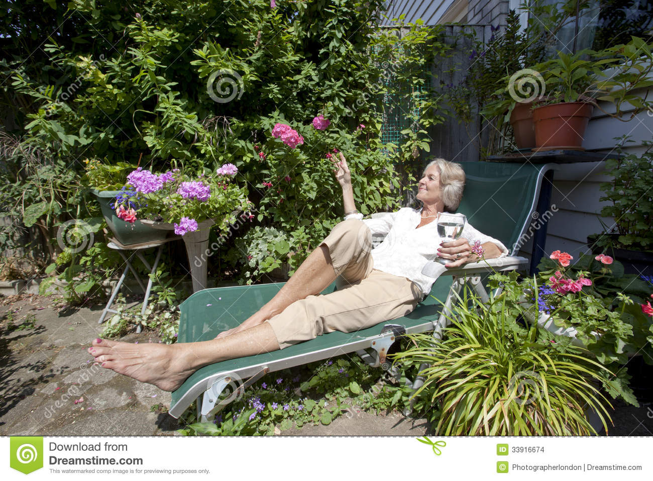 Senior Woman With Wineglass Relaxing On Lounge Chair In